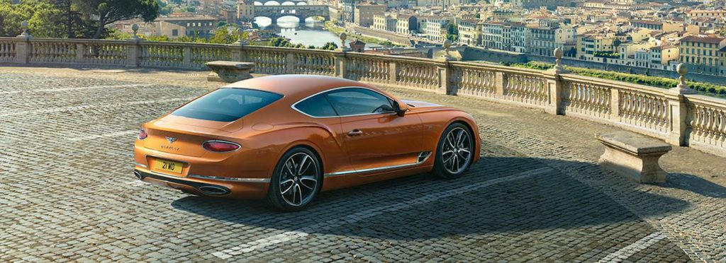 Orange Bentley Continental GT overlooking city