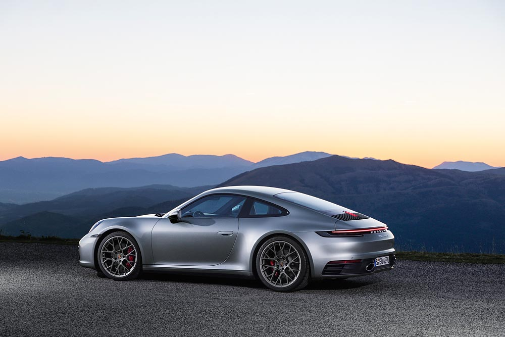 Silver Porsche 911 in front of mountains at sunrise